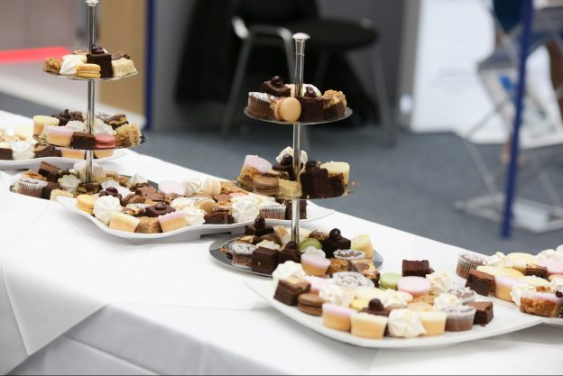 Cakes liad out as a buffet on a table with a white tablecloth