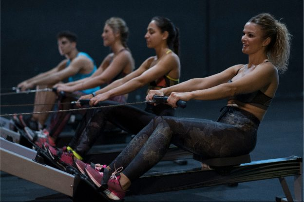 Four people rowing on rowing machines