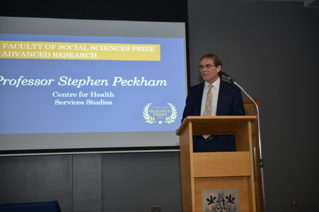 Professor Stephen Peckham standing on a podium on stage giving a talk with a projector screen behind him saying: Faculty of Social Sciences Prize and Advanced Research Professor Stephen Peckham Centre for Health Services Studies