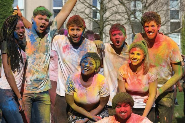 Group of students at Holi festival looking very colourful
