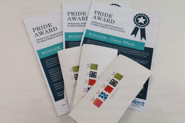 Three pride award booklets to the three Hospitality staff who each won an award