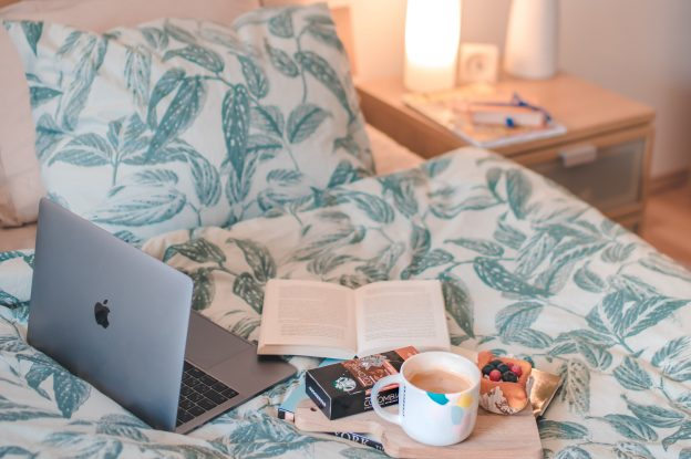 Laptop, cup of tea, open book and a fruite pastry all on a made bed, with a nightstand next to it.