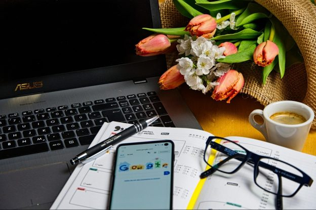 An open laptop with a pen, phone and glasses lays next on an open laptop and flowers