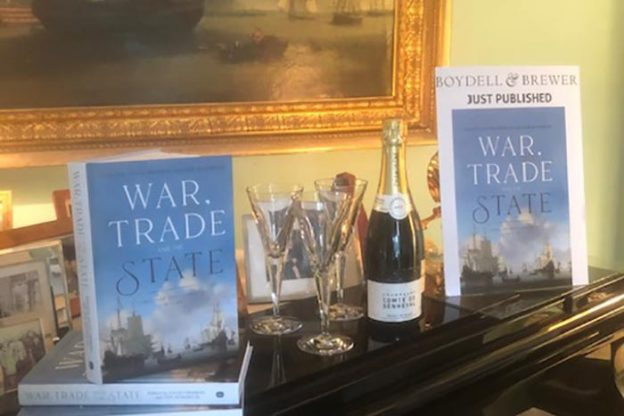 Two War, Trade and State books stacked on top of a piano with a bottle of champagne