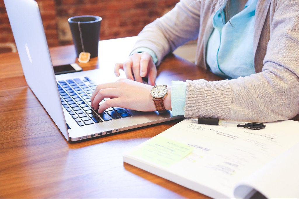 Woman typing on a laptop keyboard