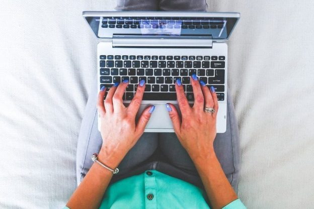 Woman typing on a laptop resting on her lap