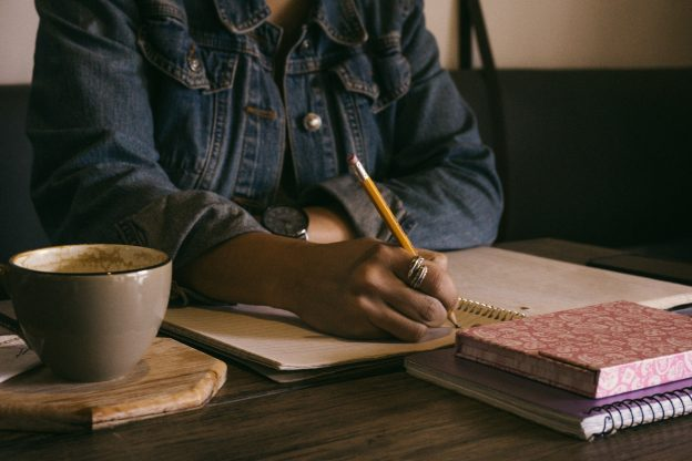 writing at a desk with hot drink