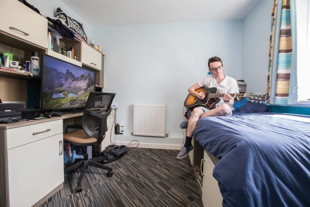 guy playing guitar in university bedroom