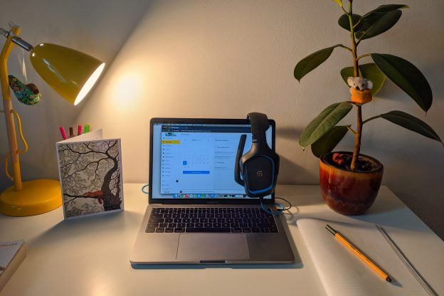 Macbook pro on white table next to a plant and yellow table lamp