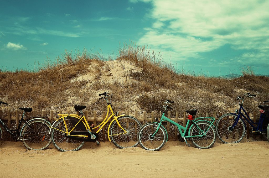 Four assorted-colour commuter bikes near a hill at daytime