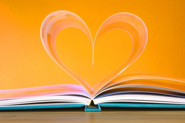 An open book with pages making the shape of a heart