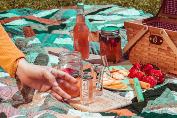 Person touching clear glass jar in a picnic setting