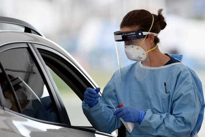 A medic person in PPE testing someone sitting in their car.