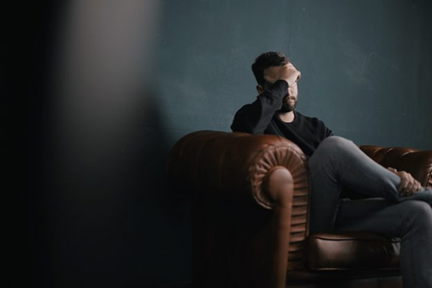 Man sitting on a sofa with his head in his hand