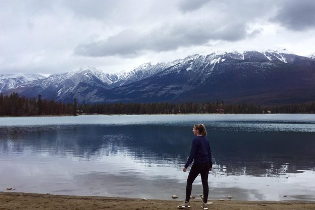 Student Alanah standing in front of lake and snow capped mountains in Canada
