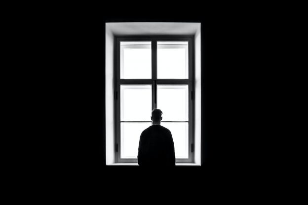 Black and white photo of person standing looking out of window from dark room