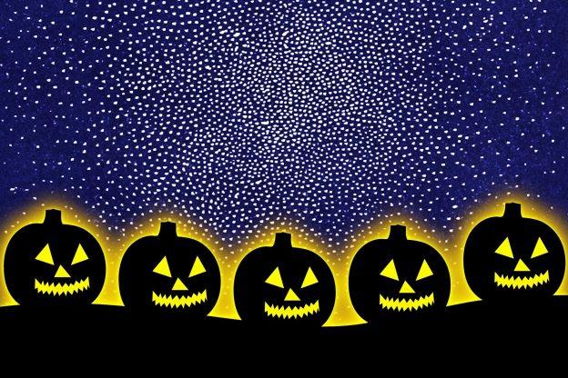 A line of smiling carved pumpkins