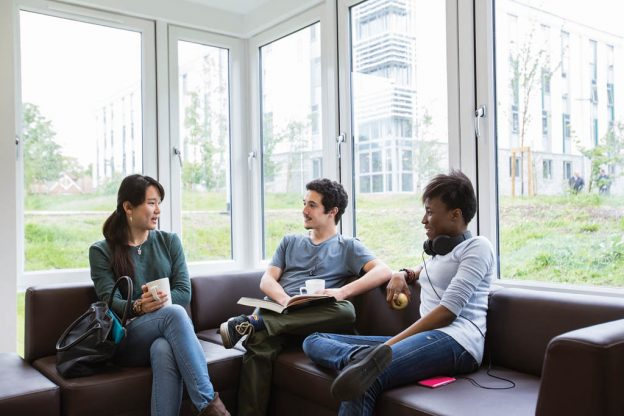 Three students sat on corner sofa together catching up