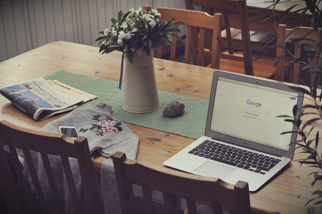 Laptop on top of table beside a vase of flowers