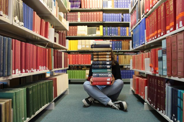 Person sat cross legged in library with pile of books stacked high