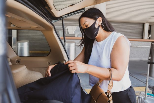 Woman in white tank top wearing a mask putting a bag in the boot of the car