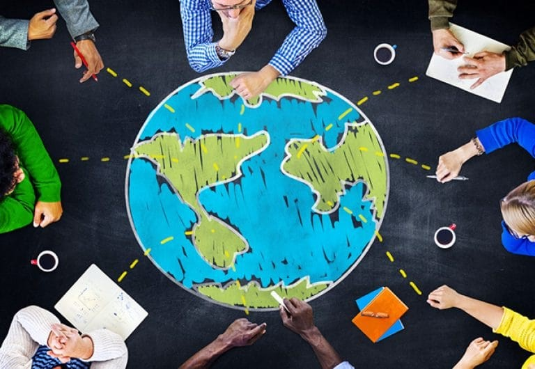 People sitting around an illustration of a globe