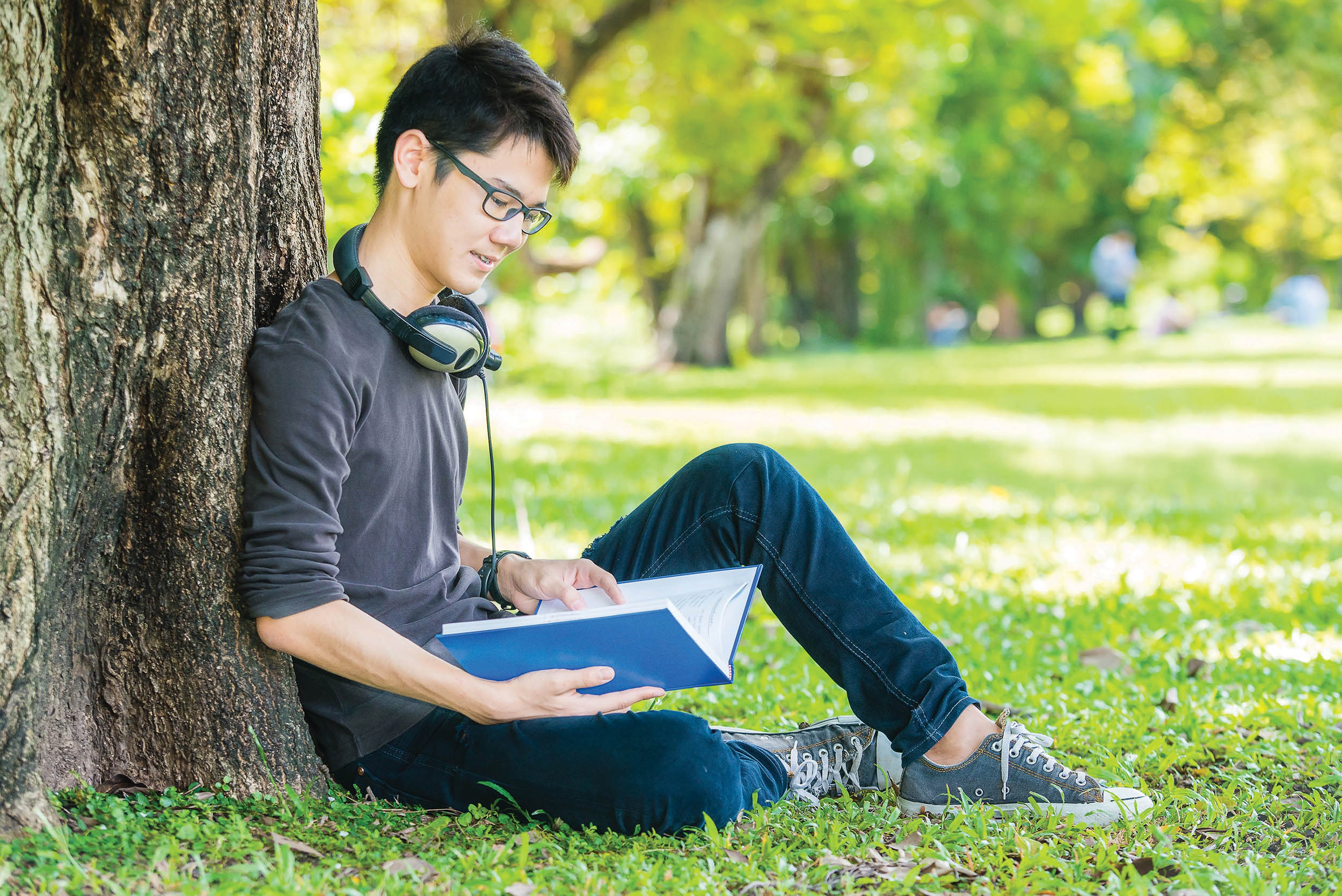 Student sat by tree