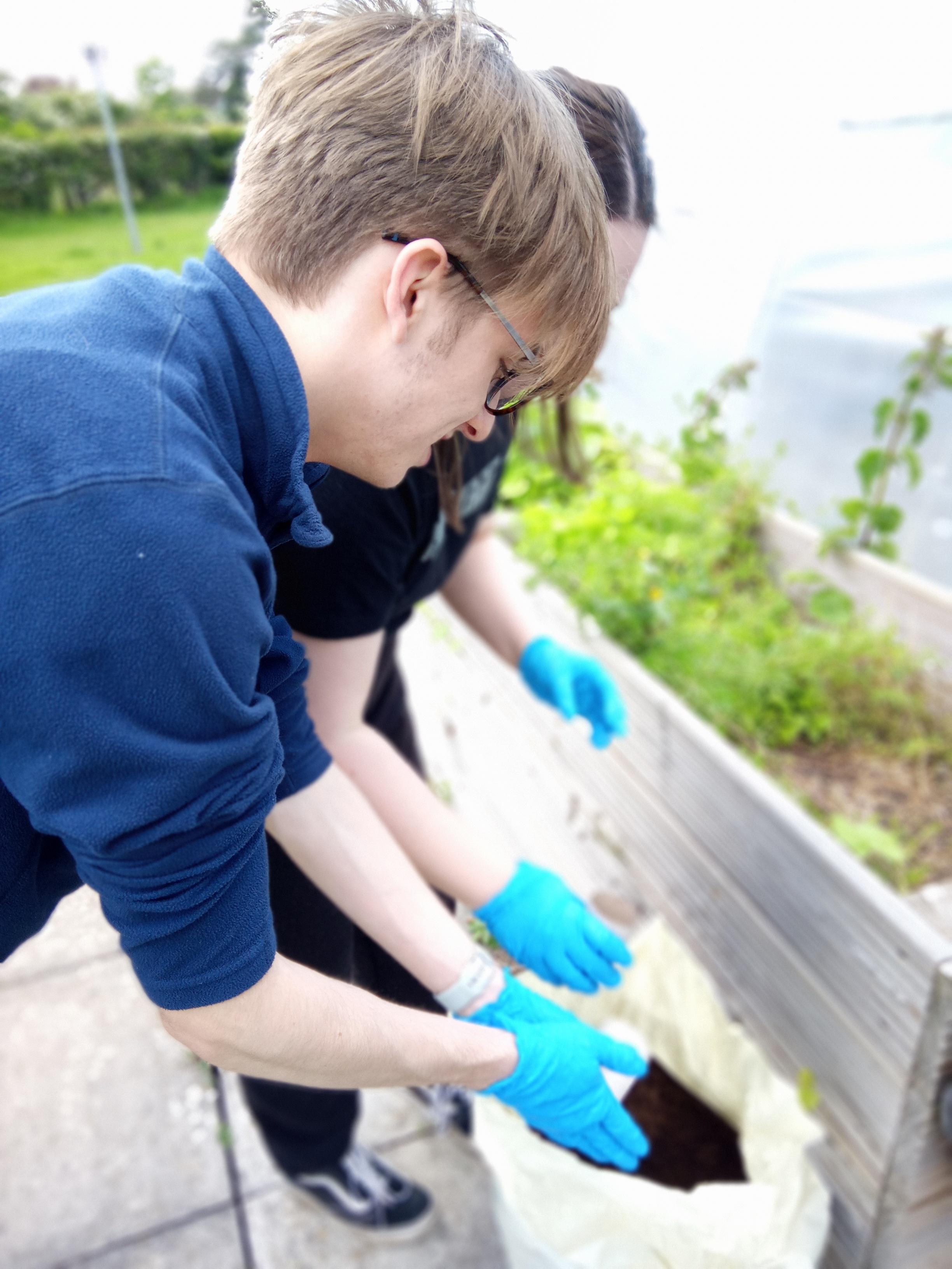 students handling soil