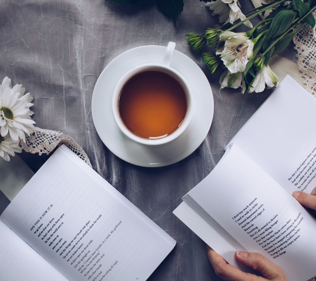 A white tea cup with flowers and 2 open books on a table.