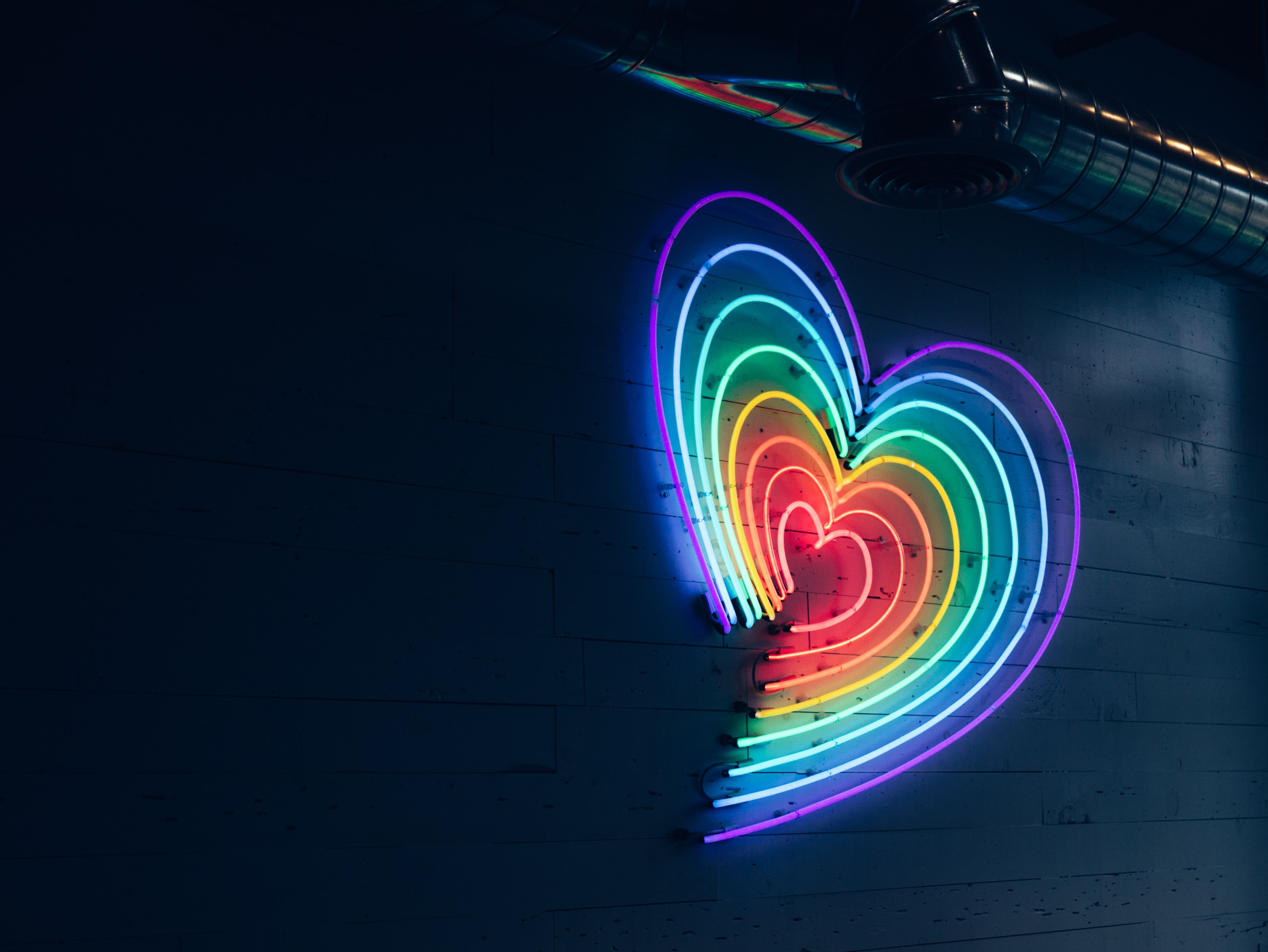 Pride Month - Neon light in the shape of a heart in the colours of the rainbow set against a wall