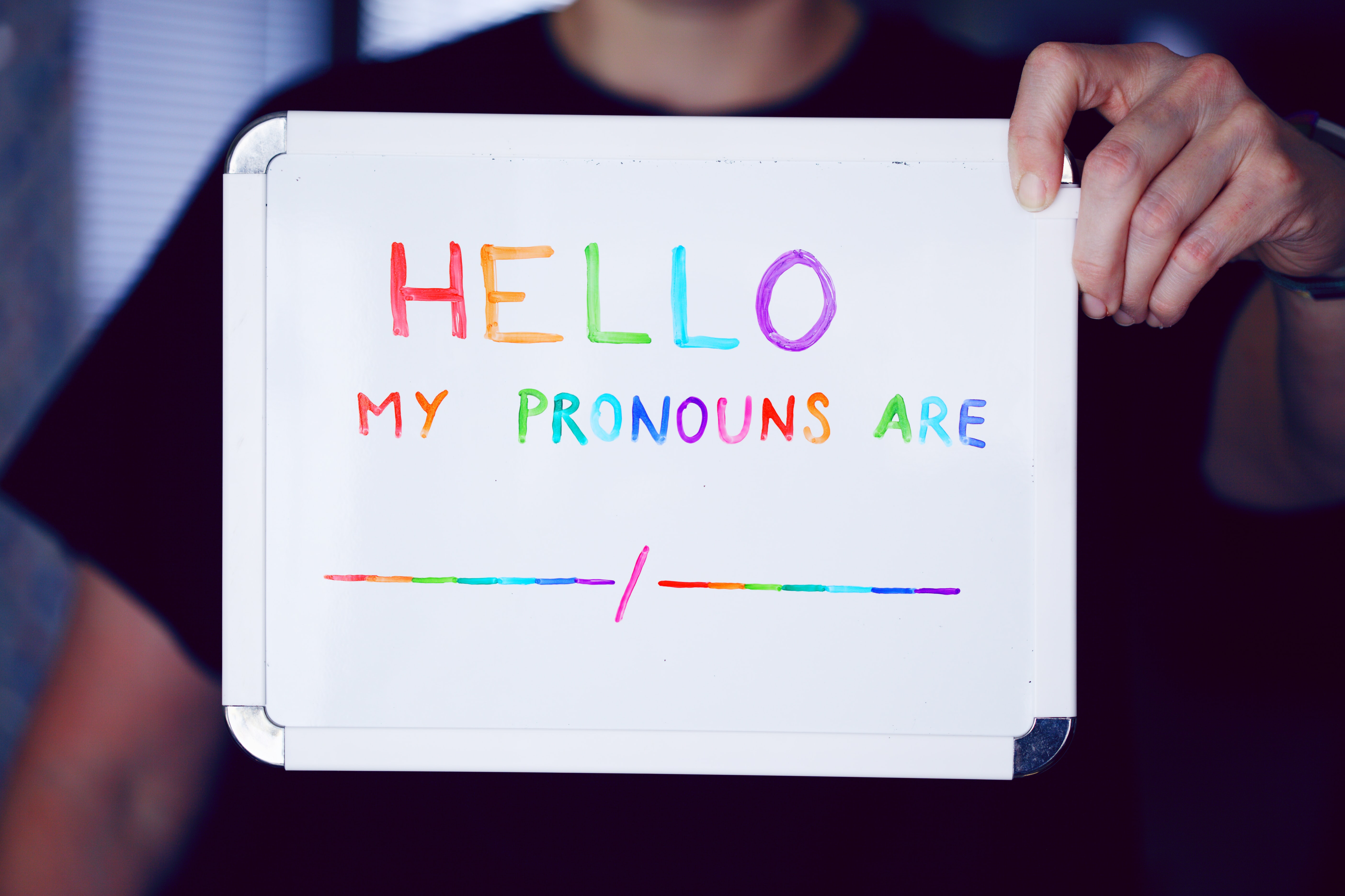 White board with Hello my pronouns are _______/ ______ in multicoloured writing