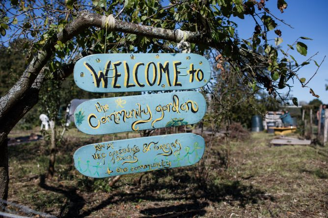Wooden sign reads: Welcome to community garden