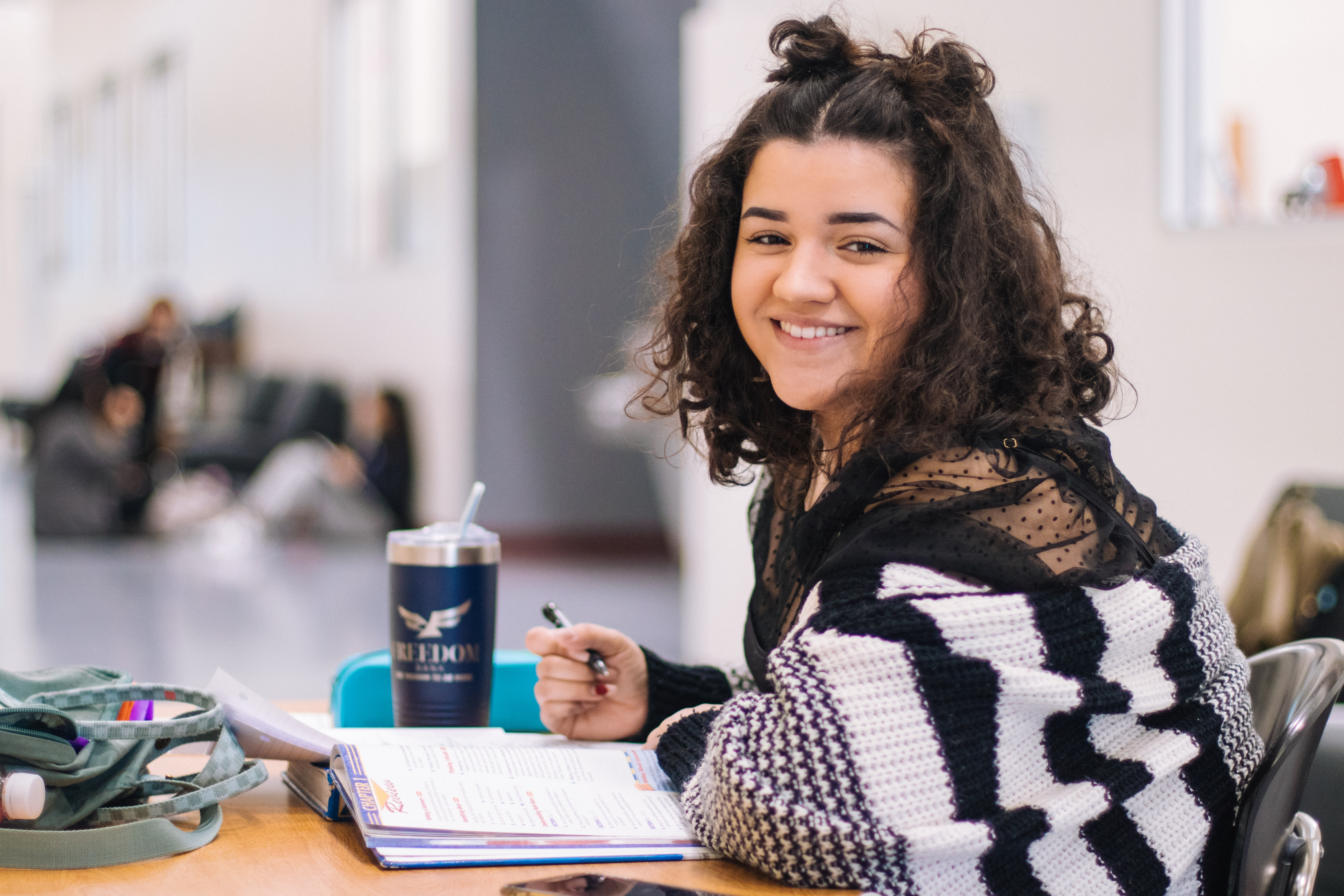 Girl wearing a black and white stripey jumper smiles at camera while studying, book open in front of her