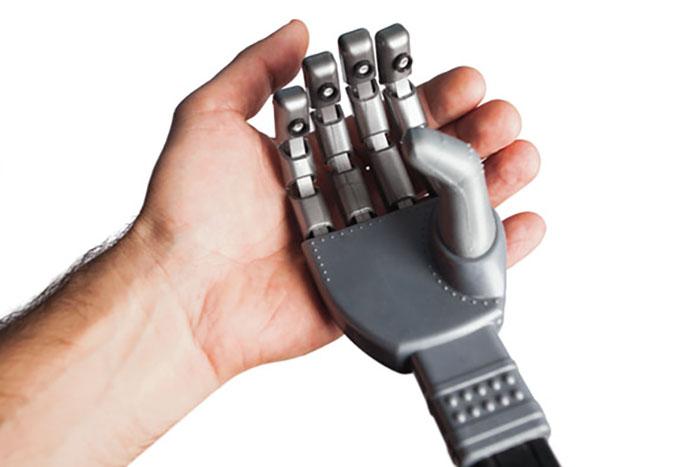 human hand holding robotic hand