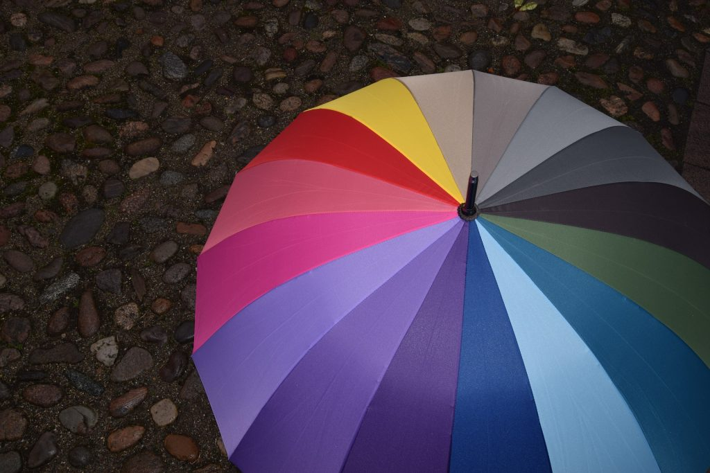 multicoloured umbrella on paving stones