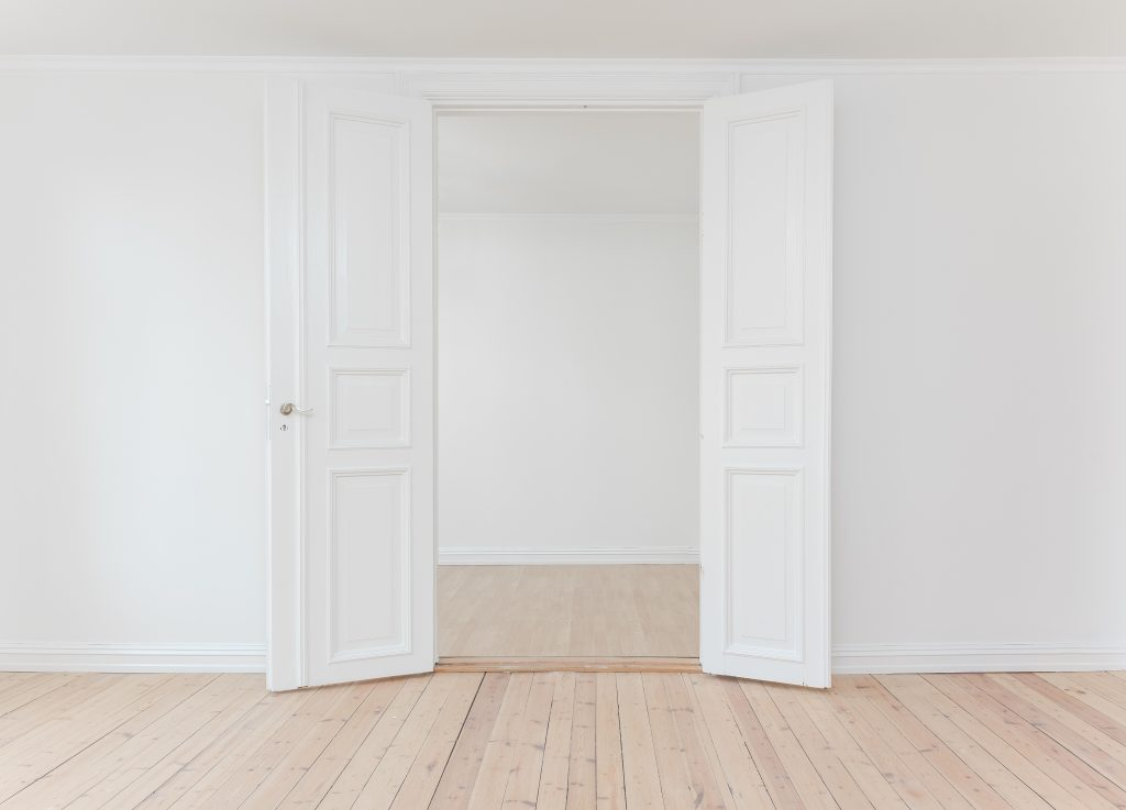 White open double interior doors, opening into another room