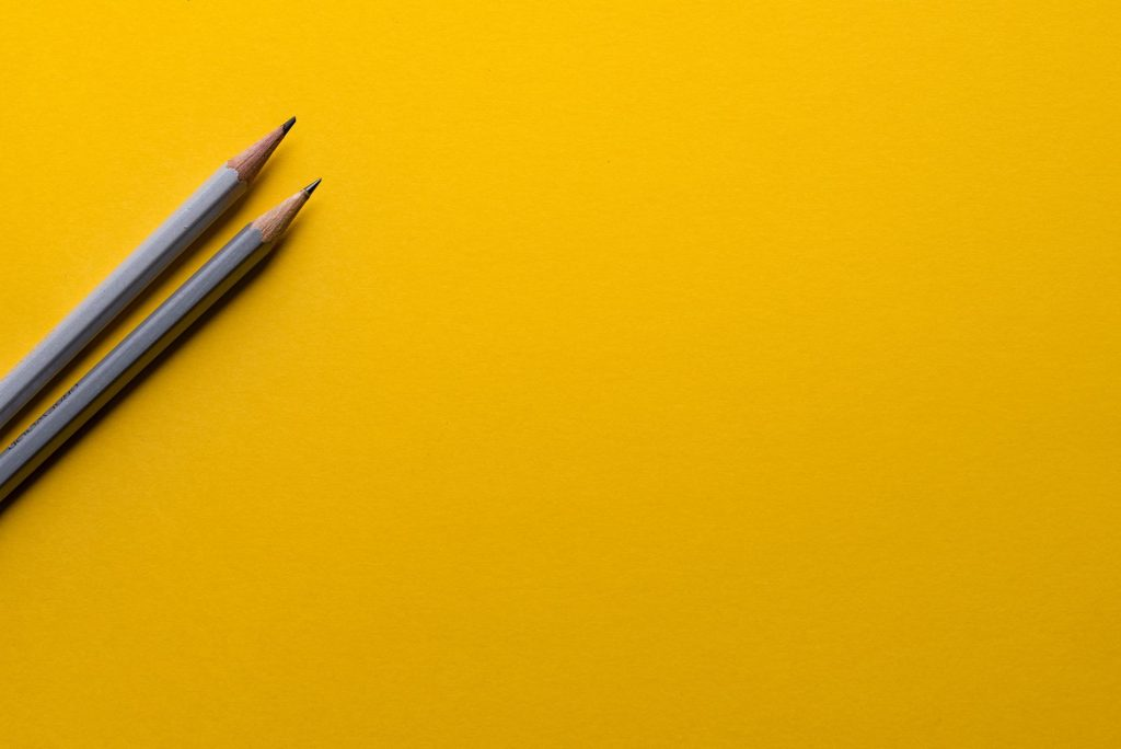 two grey pencils sit on a yellow surface