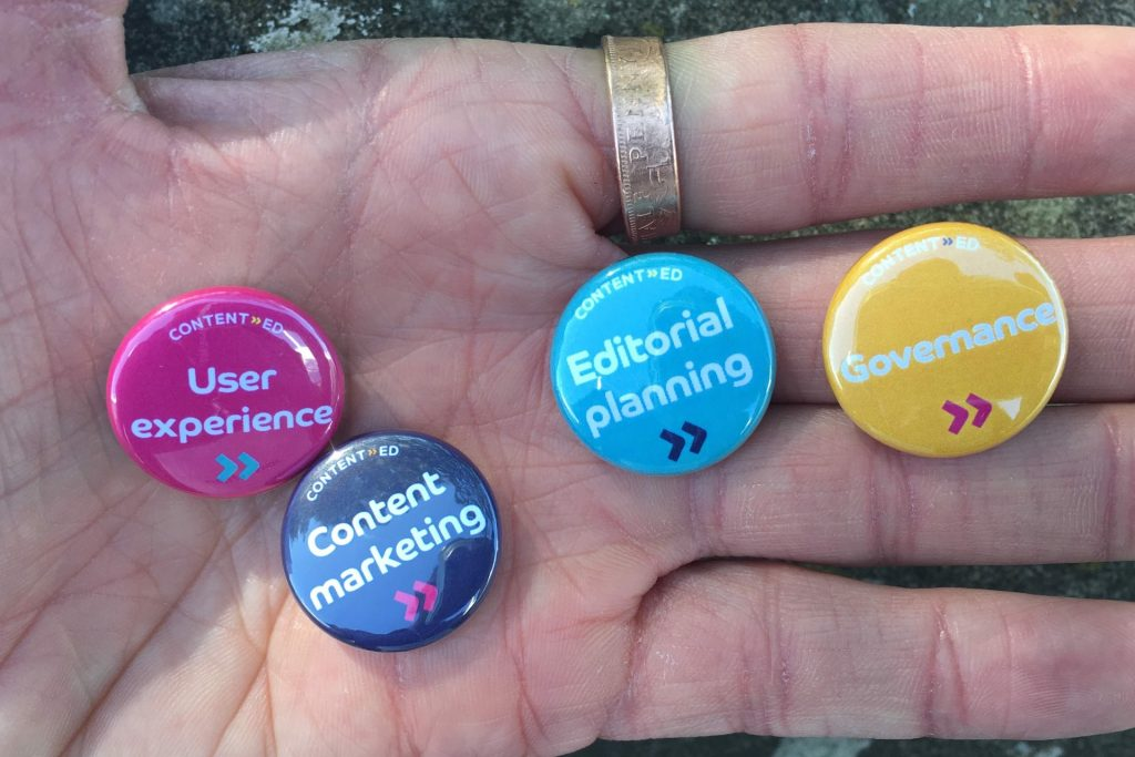 A hand showing various badges