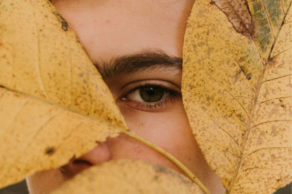 Person hiding beneath leaves